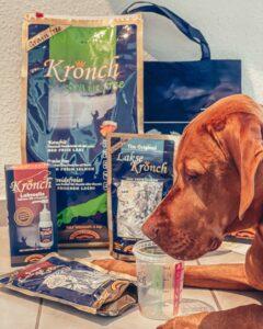 Magya liegt vor dem großen Futterpaket von Henne Pet Food